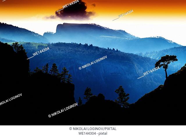 Horizontal vdramatic mountain trees on rocks silhouette sunset background backdrop