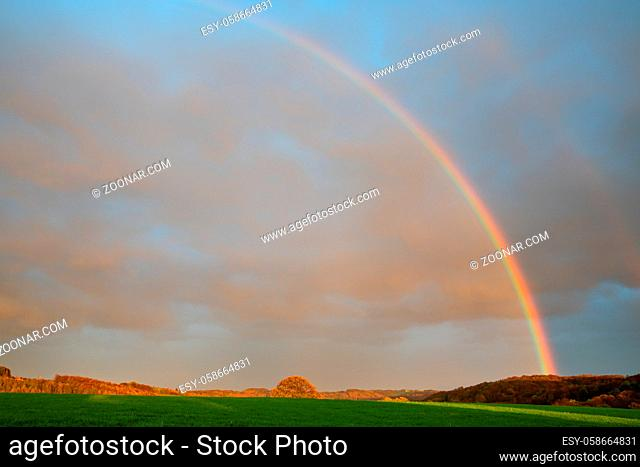 Evening landscape with rainbow and colored clouds