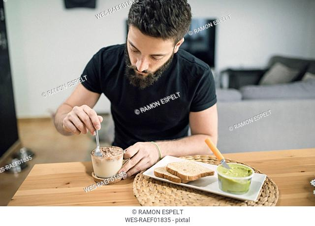 Young man preparing his breakfast at home, mixing cocoa and milk