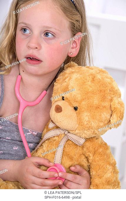MODEL RELEASED. Girl using stethoscope with teddy bear