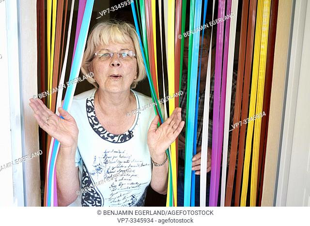 funny senior woman walking through colorful curtain stripes at home, clapping hands
