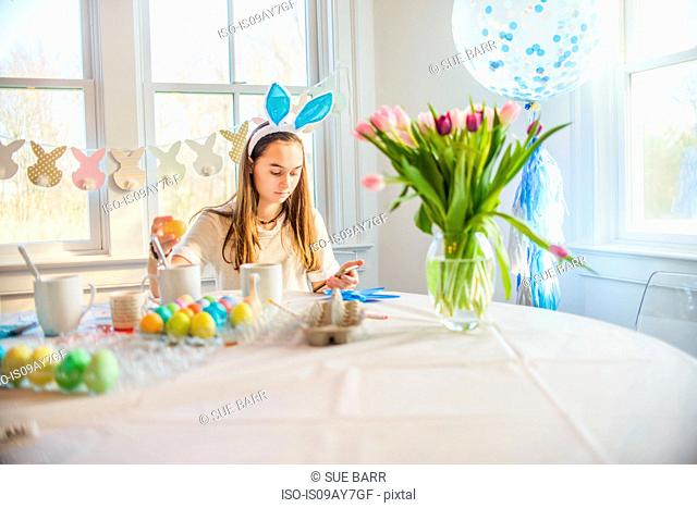 Teenage girl reading texts whilst dyeing hard boiled eggs for Easter at table