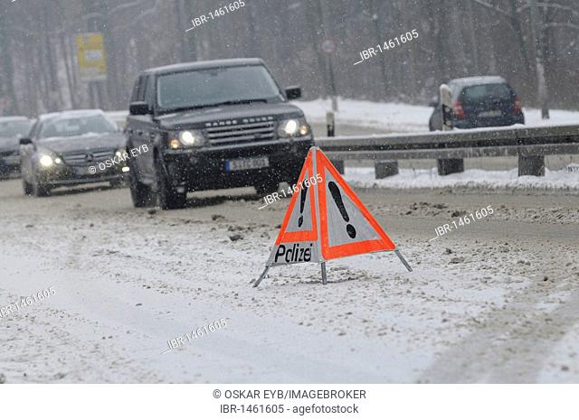 Warning triangle of the police on snow-covered road in front of a traffic jam, Stuttgart, Baden-Wuerttemberg, Germany, Europe