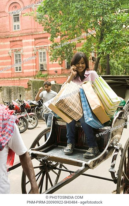 Woman holding shopping bags and talking on a mobile phone, Kolkata, West Bengal, India