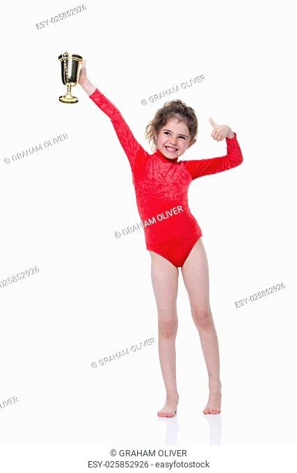 Young gymnast in a red leotard holding up a trophy on a white background. She is looking at the camera and smiling