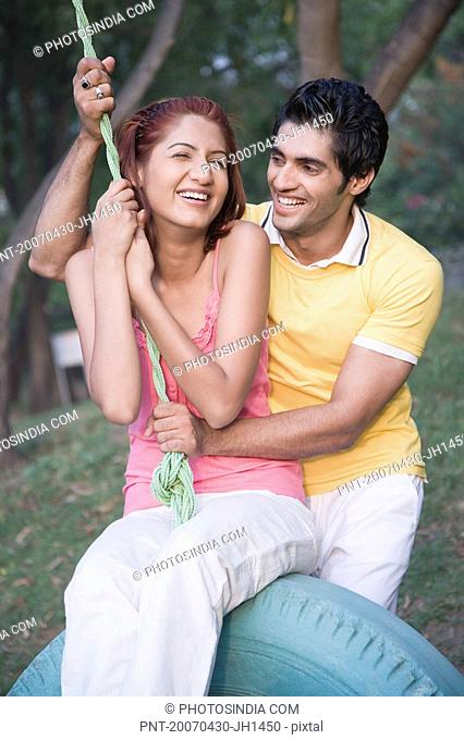 Young man pushing a young woman on a tire swing