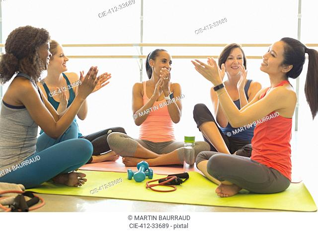 Smiling women clapping in gym studio