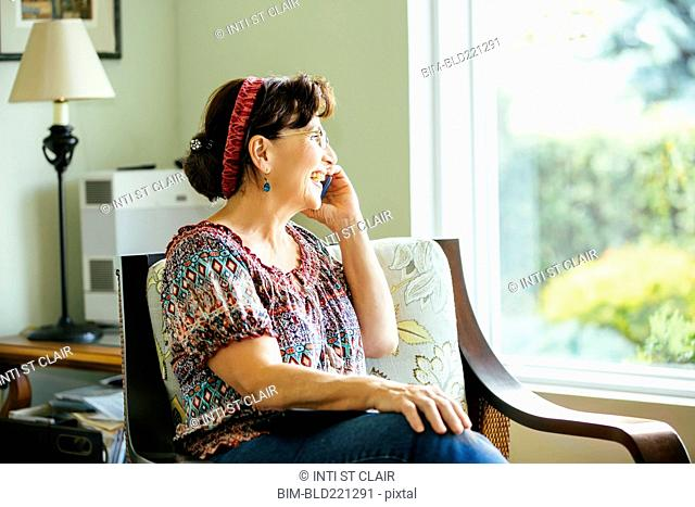 Caucasian woman talking on cell phone in armchair