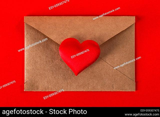 Valentine day love letter, envelope of craft paper with red heart on red background