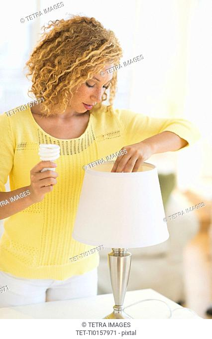 Young woman changing bulb in lamp