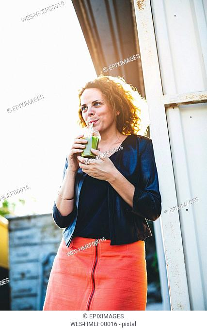 Portrait of woman drinking green smoothie outdoors