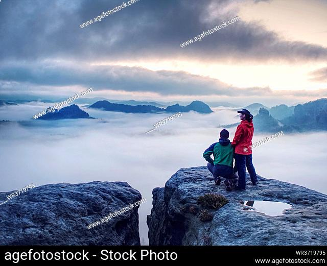 Night photo A woman shows magical lightning lantern to her man. Woman sits on a rock and shines to misty darkness. First Sun rays appear in the clouds