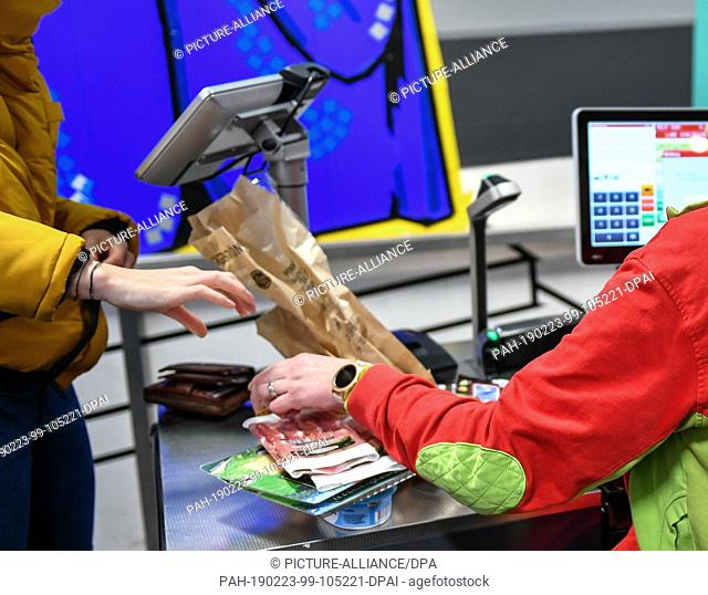 22 February 2019, Berlin: A cashier and a customer at the checkout in the food discounter Penny in Boxhagener Straße. Photo: Jens Kalaene/dpa-Zentralbild/dpa