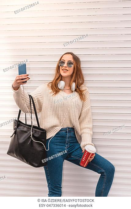 Beautiful attractive young girl in jumper and jeans with takeaway coffe, headphones and sunglasses takes selfie on a wall