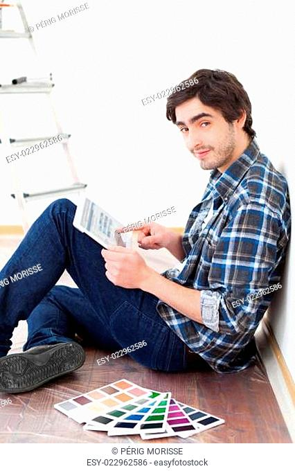 Young man using tablet while choosing color of his flat