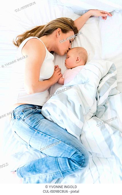 Mother kissing sleeping baby in bed