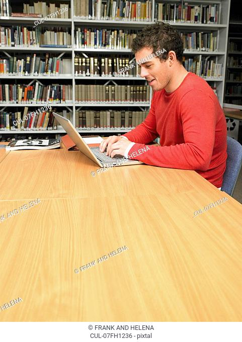 Young man working at computer in library