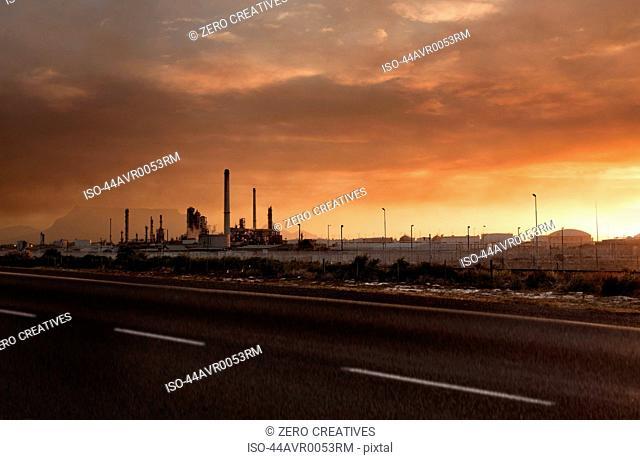 Sun setting over power station