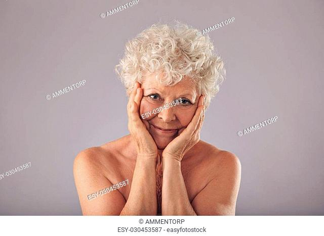 Portrait of senior caucasian woman touching her face against grey background. Feeling happy for her skin condition at old age