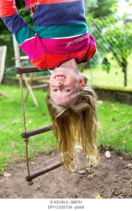 A young girl wearing a colourful shirt hangs upside down from a rope ladder outside on a summer day; Darmstadt, Hessen, Germany