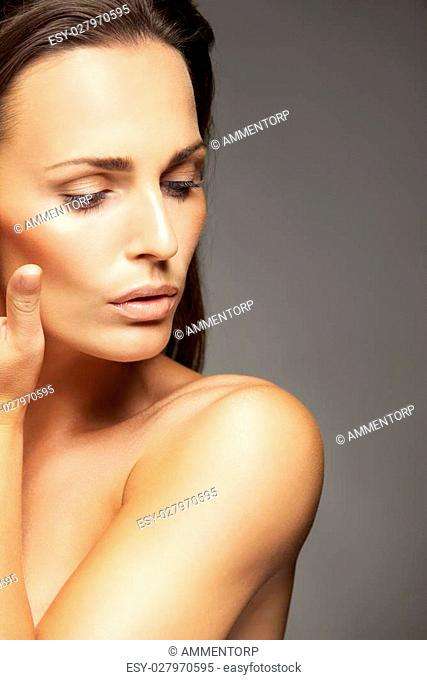 Portrait of a beautiful woman touching her face agaisnt grey backgruond. Pretty young female model with clean and healthy skin