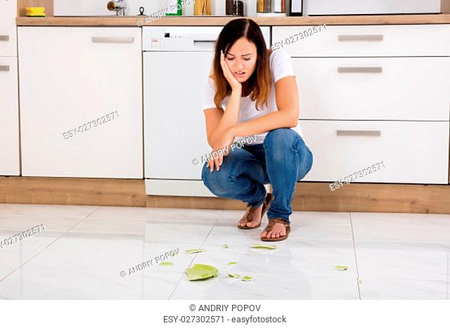 Young Unhappy Woman Looking At The Broken Plate Fallen On Floor In The Kitchen