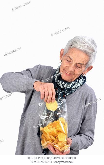 senior woman eating chips on white