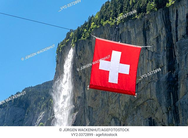 Swiss flag in front of the Staubbach Falls, Bernese Oberland, Switzerland, Europe
