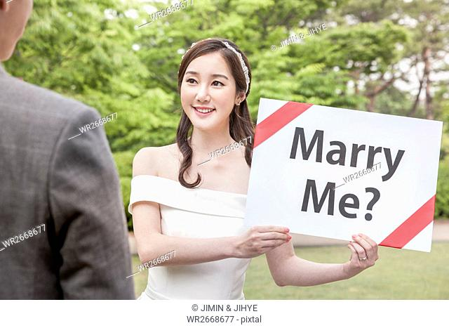 Young smiling wedding couple with English message face to face outdoors