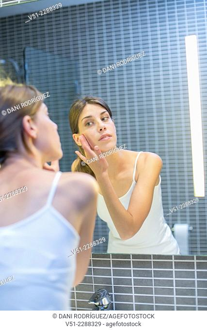 Young woman in bathroom putting on creme in front of a mirror