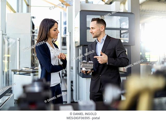 Businessman and businesswoman discussing workpiece in factory