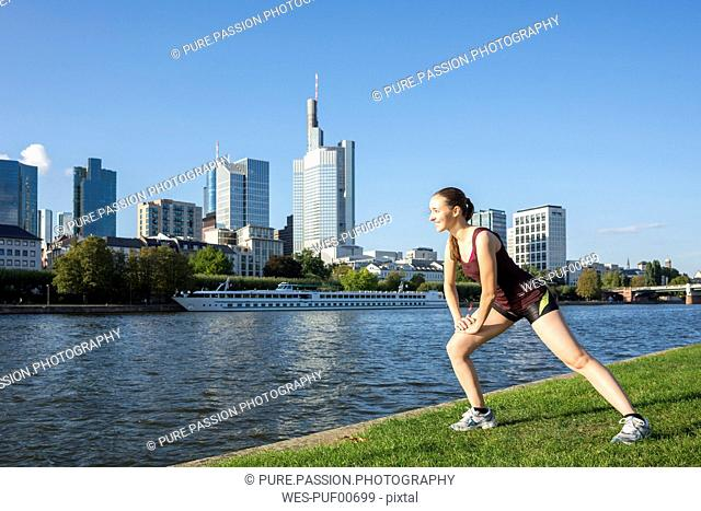 Germany, Frankfurt, young woman stretching at riverside