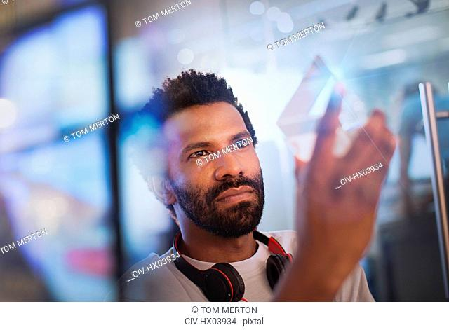Focused, innovative male entrepreneur examining glass triangle prototype