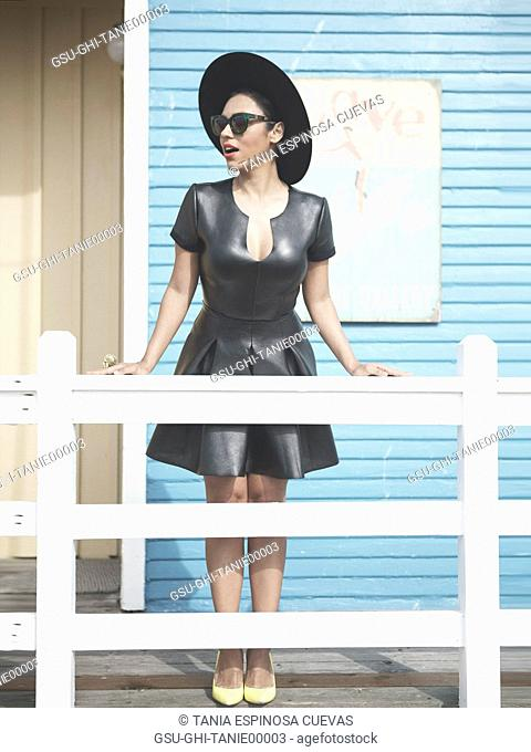 Woman in Black Leather Dress, Hat and Sunglasses with Astonished Look Standing at Deck Railing
