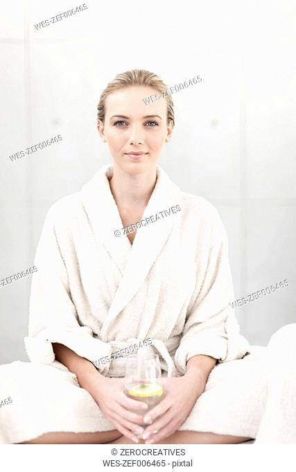 Portrait of smiling young woman with bathrobe and glass of water