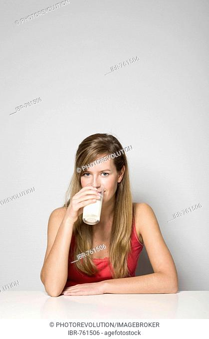 Young woman sitting at a table drinking a glass of milk