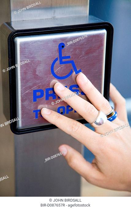 Woman's hand on a disability access door button
