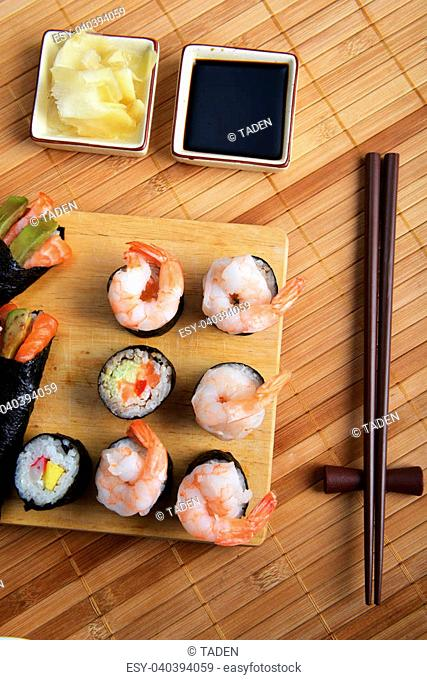 tasty fresh sushi rolls on wooden plate