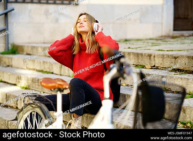 Blond woman listening music through headphones while sitting on steps