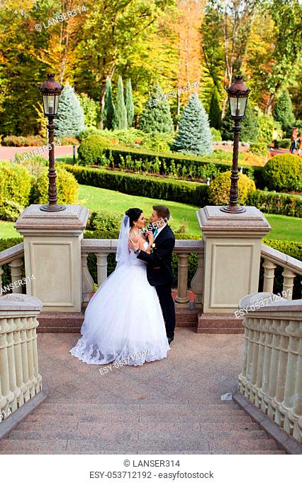 The groom tenderly embraced the happy bride in the summer park