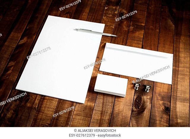 Photo of blank stationery set on wooden table background. Blank letterhead, business cards, envelope and pen. Mock up for branding identity