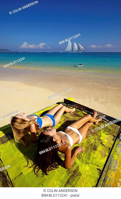 Women relaxing on raft on beach
