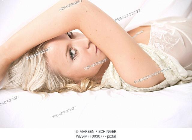 Blond woman in lingerie lying on bed