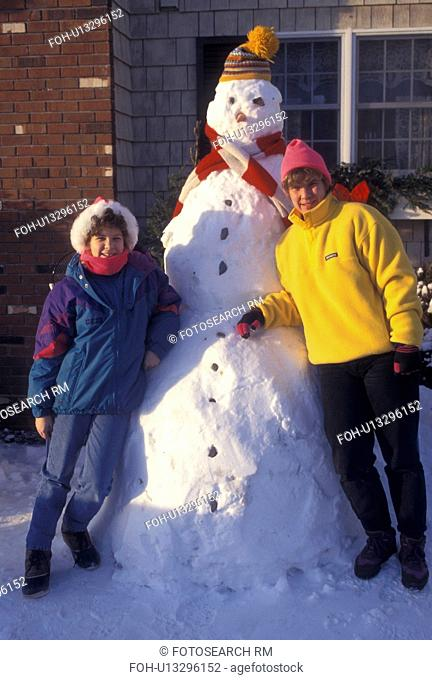 snowman, Vermont, VT, Mother and daughter pose for picture with tall snowman in Montpelier in winter