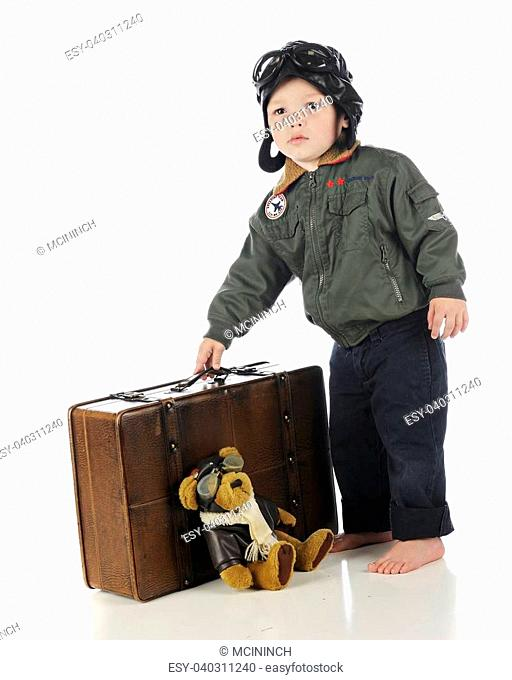 An adorable toddler in his old-time pilot outfit picking up his suitcase. On a white background
