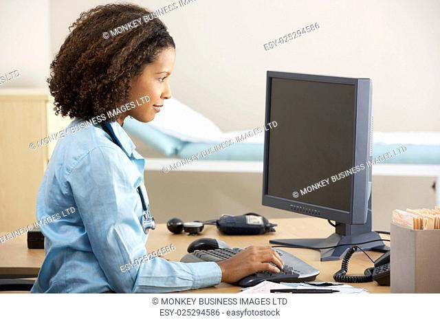 Young female Doctor working on computer at desk