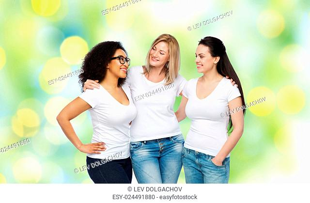 friendship, diverse, body positive, communication and people concept - group of happy different size women in white t-shirts hugging and talking over green...