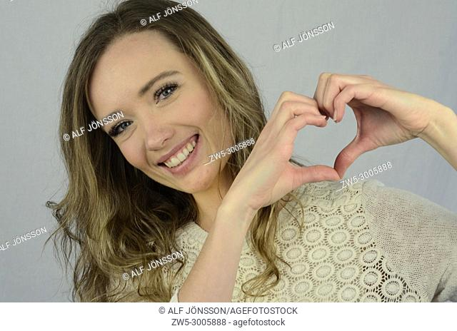 Young happy woman shape a heart with her hands