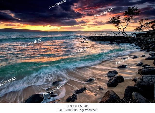 A dramatic sky at sunset over a turquoise ocean along the coast of a hawaiian island; Hawaii, United States of America