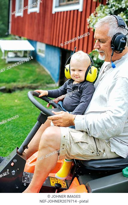 Grandfather with grandson on ride-on lawn mower